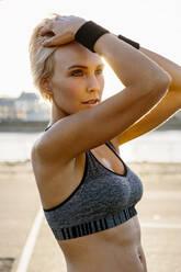 Portrait of blonde sportswoman, hands in hair - MADF01426