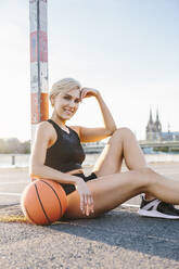 Blonde woman sitting with basketball on playing field in Cologne, Germany - MADF01432