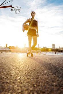 Blonde woman with basketball against the sun, Cologne, Germany - MADF01435