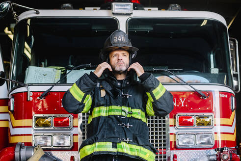 USA, New York, Portrait of firefighter putting on helmet in front of fire engine - CJMF00184