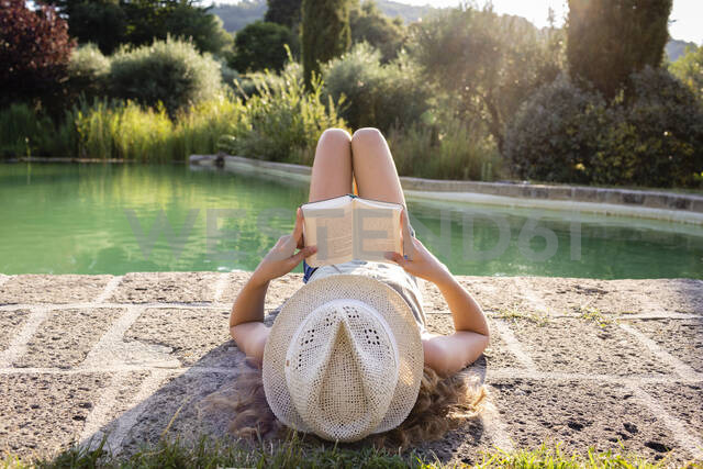 Girl with straw hat lying at swimming pool, reading a book - OJF00361 - Julia Otto/Westend61