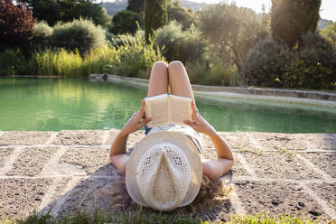 Girl with straw hat lying at swimming pool, reading a book - OJF00361