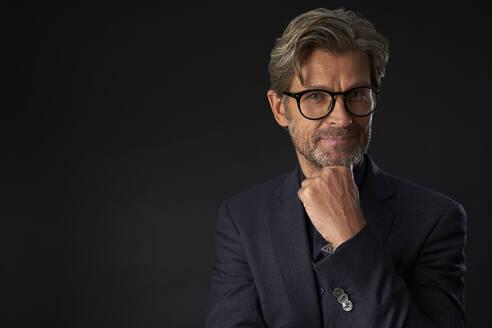 Portrait of mature businessman wearing glasses against dark background - PHDF00007