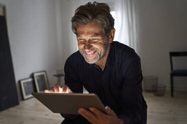 Portrait of smiling mature man having fun with digital tablet at home - PHDF00013
