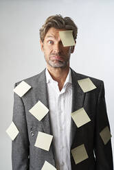 Portrait of helpless businessman with note papers stucking on his forehead and his suit coat - PHDF00016