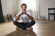 Portrait of smiling mature man sitting on the floor at home - PHDF00019