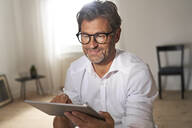 Portrait of smiling mature man wearing glasses using digital tablet at home - PHDF00022