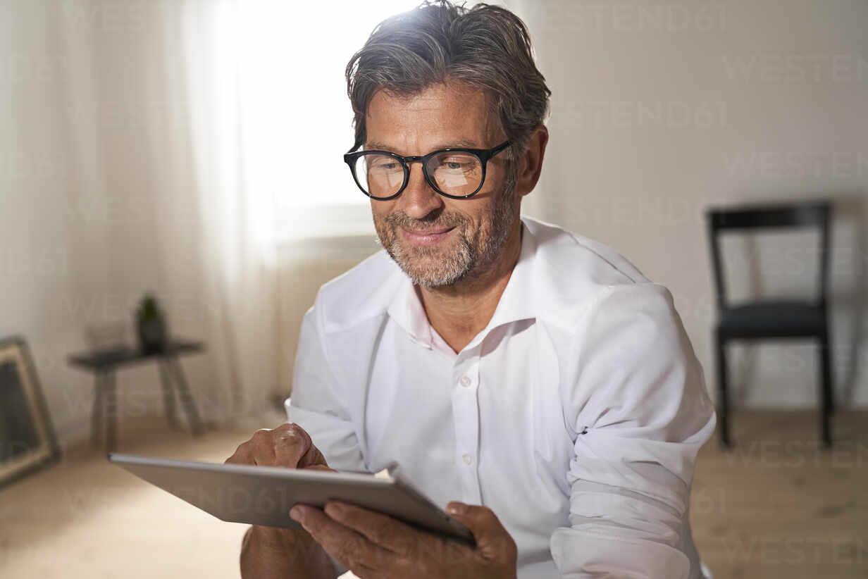 Portrait of smiling mature man wearing glasses using digital tablet at home - PHDF00022 - Isabella Bellnini/Westend61