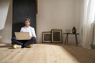 Relaxed mature man sitting on the floor at home using laptop - PHDF00025