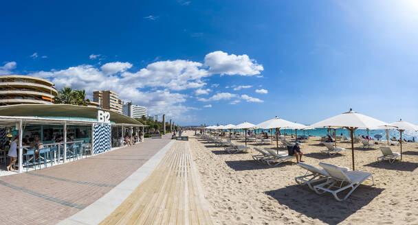 Spain, Mallorca, Camp de Mar, Rows of deckchairs and beach umbrellas along Playa de Palma in summer - AM07549