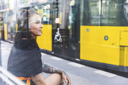 Portrait of tattooed young woman waiting at tram stop, Berlin, Germany - WPEF02369