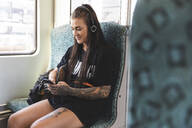 Tattooed young woman sitting in commuter line using smartphone and headphones, Berlin, Germany - WPEF02372