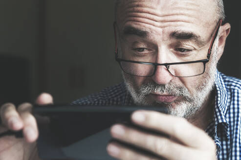 Senior man using smartphone at home - FRF00900