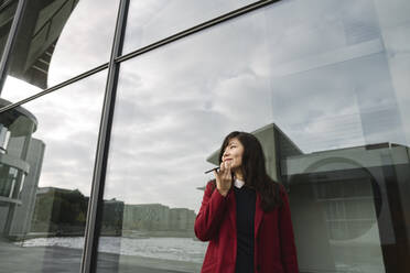 Businesswoman standing near to modern building and using smartphone - AHSF01520