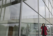 Businesswoman standing near to modern building and using smartphone - AHSF01523