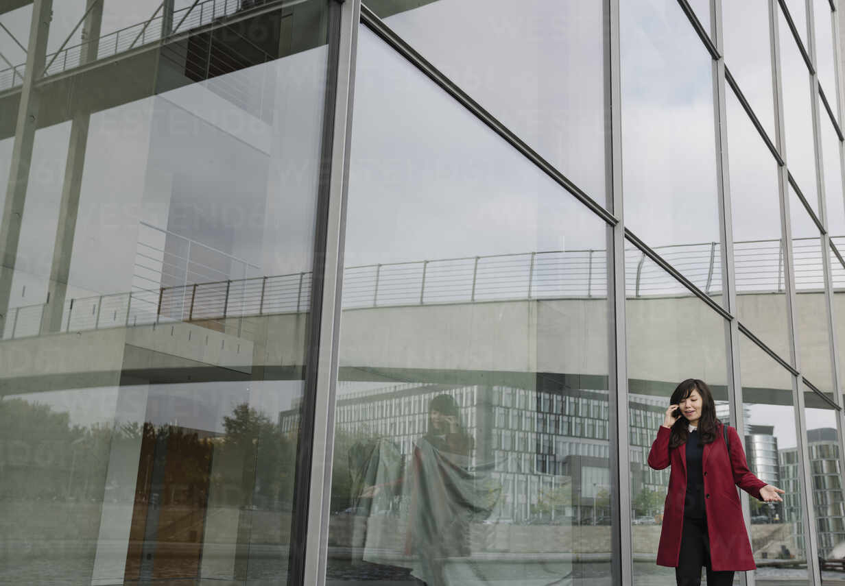 Businesswoman standing near to modern building and using smartphone - AHSF01523 - Hernandez and Sorokina/Westend61