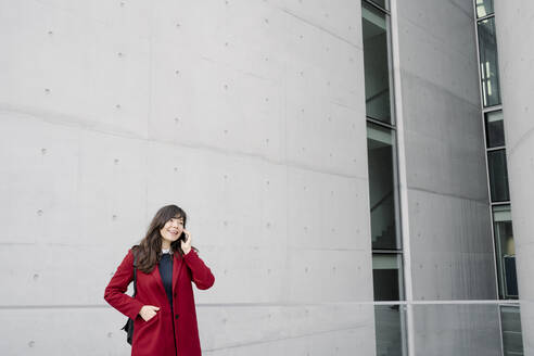 Businesswoman standing near to modern building and using smartphone - AHSF01526
