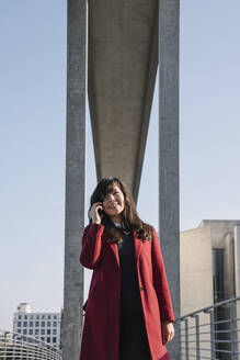 Businesswoman standing near to modern building and using smartphone - AHSF01541