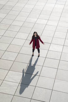 View from above of walking modern businesswoman standing on concrete floor with arms open - AHSF01544