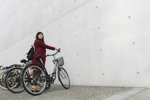 Businesswoman taking bicycle in the background of modern building - AHSF01550