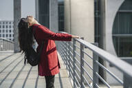 Modern businesswoman getting relaxed standing on a bridge, Berlin, Germany - AHSF01553