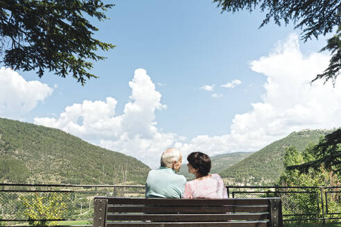 Back view of senior couple sitting on a bench looking at each other, Jaca, Spain - AHSF01562