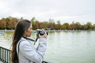 Woman standing at a lake taking a photo - KIJF02837