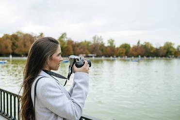 Woman standing at a lake taking a photo - KIJF02837