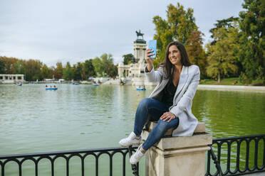 Woman taking a selfie in El Retiro park, Madrid, Spain - KIJF02840