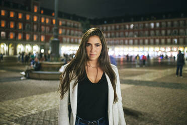 Portrait of a woman standing on Plaza Mayor at night, Madrid, Spain - KIJF02846