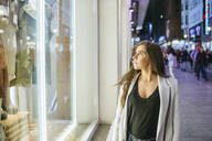 Woman looking at shop window in clothing store at night - KIJF02849