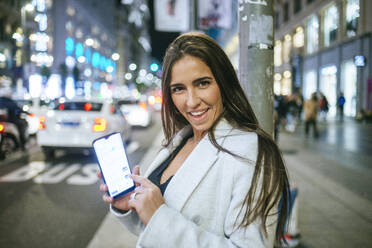 Happy woman showing her smartphone in the street at night - KIJF02852