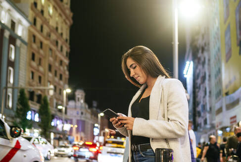 Woman using her smartphone in the street at night - KIJF02855