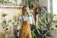 Young woman caring for plants in a small shop - VPIF01830