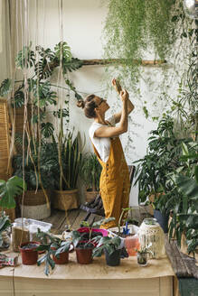 Young woman caring for plants in a small shop - VPIF01836