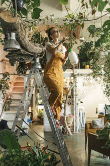Young woman standing on a ladder caring for plants in a small shop - VPIF01842