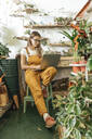 Young woman using laptop in a small gardening shop - VPIF01851