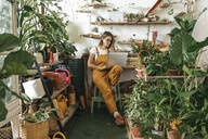 Young woman using laptop in a small gardening shop - VPIF01854