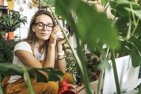 Young woman having a coffee break in a small gardening shop - VPIF01857
