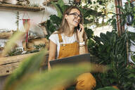 Laughing young woman on the phone in a small gardening shop - VPIF01860