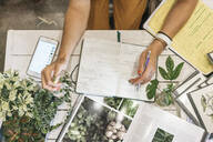 Top view of woman taking notes in a small gardening shop - VPIF01863