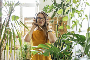 Young woman surrounded by plants listening to music with headphones - VPIF01875