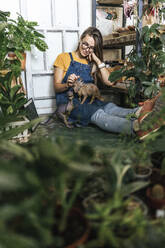 Young woman with dinosaur figurine sitting on the floor in a small shop with plants - VPIF01887