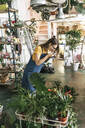 Young woman taking pictures of plants in a small gardening shop - VPIF01890