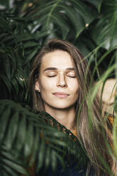 Portrait of a young woman with closed eyes amidst green plants - VPIF01893