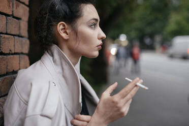 Profile of pensive woman with cigarette outdoors - EYAF00713