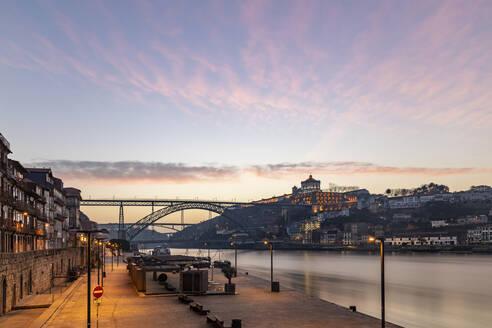 Portugal, Porto District,Porto, Douro river harbor at dawn with city buildings and Dom Luis I Bridge in background - WPEF02409