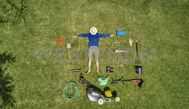 View from above of a gardener with sun hat on his face, laying on the grass with all the tools he need for take care of garden - VEGF00986 - Veam/Westend61