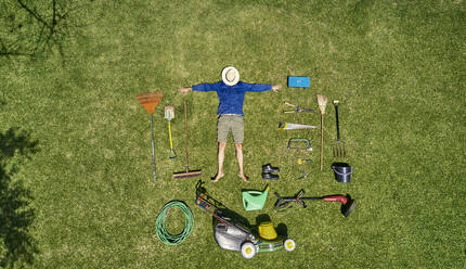 View from above of a gardener with sun hat on his face, laying on the grass with all the tools he need for take care of garden - VEGF00986