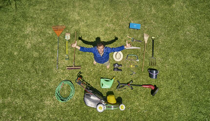 View from above of a gardener in standing on meadow with all the tools he need for take care of garden - VEGF00989